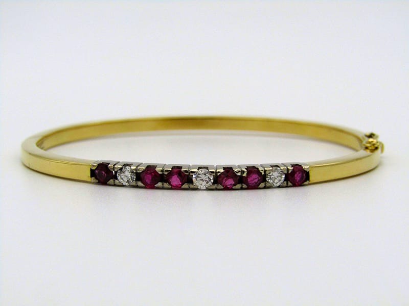 18kt yellow gold catch bangle set <br>with 6 rubies and 3 diamonds. Circa 1950.<br>Gross weight: 11,2 grams <br>Rubies: 0.90cts in total <br>Diamonds: 0.36cts in total .