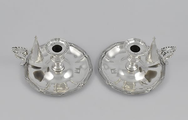Pair of Victorian silver chamber candlesticks<br>marked for London 1838 by Paul Storr.<br>They are also later marked with the French<br>control mark for Imports, in use<br>from 1 July 1864- 30 June 1893. The base<br>marked with a pattern number-120