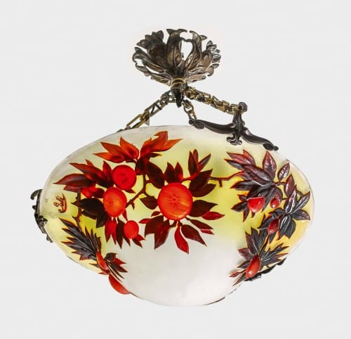 Rare Blow-out 'Oranges' Plaffonier<br>By Emile Gallé Circa 1900.<br>A magnificent double-overlaid, acid-etched<br>and carved mould-blown chandelier,<br>with orange/red oranges against an<br>amber and white ground, with dark leaves,<br> suspended on original bronze chains<br>with three mounts, and a ceiling rose. <br>The bronze metalwork is superb,<br>obviously designed by Gallé to echo<br>the design in the glass.<br>Diameter: 45 cms<br>Signatures: Cameo 'Gallé' on side of vessel.<br>Reference: (i) Victor Arwas, 'Glass<br>Art Nouveau to Art Deco', <br>Academy Editions, 1987, pgs. 106-153.<br>(ii) Alistair Duncan & Georges de Bartha,<br>, 'Glass by Gallé', Harry N Abrams Inc.,1984,<br>pictured pg.169.