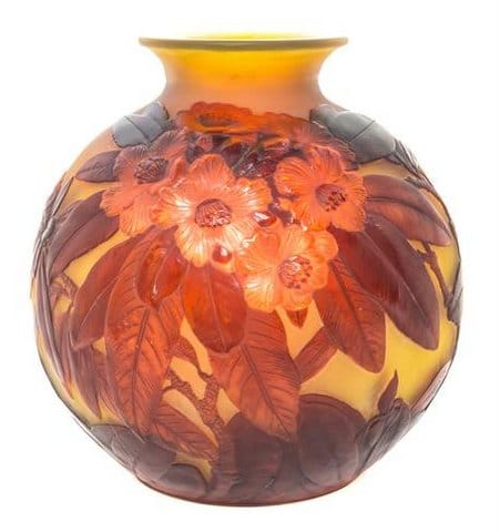 Blow-out Rhododendron Vase<br>By Emile Gallé Circa 1900<br>An overlaid, acid-etched and carved<br>blow-out (soufflé) vase, the decoration<br>in high relief, of red rhododendron<br>blossoms with foliage.The ground colour<br>is a rich yellow amber, the leaves<br>in dark shades, and the flowers in red.<br>Height:  26 cms<br>Signatures:  Cameo 'Gallé' on side of vessel.<br>Reference:  (i) Victor Arwas, 'Glass<br>Art Nouveau to Art Deco',<br>Academy Editions, 1987, pgs. 106-153.<br>(ii) Alastair Duncan & Georges de Bartha,<br>, 'Glass by Galle', Harry N Abrams<br>Inc Publishers New York,1084, pg 157, fig. 219.