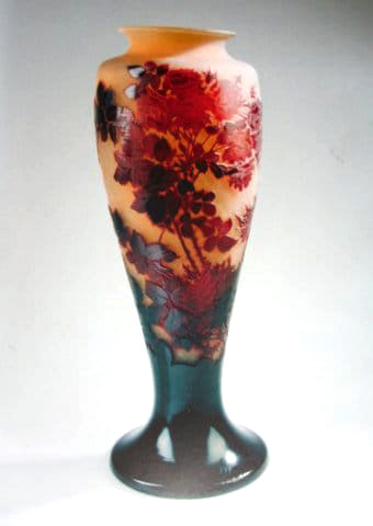 Red 'Roses Grimpantes' Vase<br>By Emile Gallé Circa 1900<br>A monumental double overlaid,<br>acid-etched and carved vase,<br>with bright red Roses Grimpantes<br>(also known as Climbing Roses),<br>the flowerheads in red, the stems<br>and leaves in dark shades,<br>on an amber ground.<br>Height:  59.5 cms<br>Signatures:  Cameo 'Gallé' on side of vase<br>Reference:  Victor Arwas, 'Glass<br>Art Nouveau to Art Deco', <br>Academy Editions, 1987, pgs. 106-153.