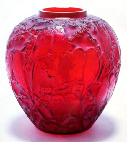 Red Perruches<br>By Rene Lalique First executed in 1919<br>A rare rich ruby red vase of spherical shape,<br>with a wide foot and small aperture,<br>the design of pairs of lovebirds<br>sitting amongst flowering branches.<br>The slight remains of a white<br>patina is in the recesses,<br>accentuating the design.<br>Height:  26 cms<br>Signatures:  Engraved script 'R Lalique' on base<br>Reference: (i) Felix Marcilhac,<br>Rene Lalique – Catalogue Raisonne<br>Des Oeuvres de Verre, Paris,<br>1989, p. 410, 876.<br>(ii) Patricia Bayer & Mark Waller,<br>The Art of Rene Lalique, 1988<br>p. 149 #272.