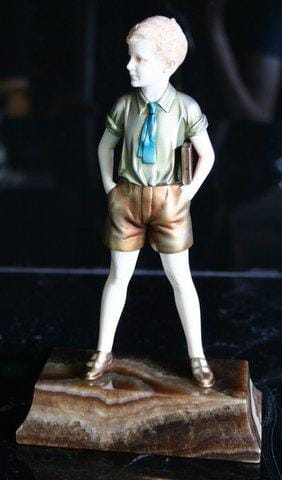 Bronze & ivory figure 'Sonny Boy'<br>By Ferdinand Preiss Circa 1920<br>A bronze and ivory figure of a young boy, <br>obviously in his school uniform, carrying<br>a book under his left arm.<br>His shorts are in gold, his shirt in a pale green, <br>and his tie is blue. He is standing on<br>a brown onyx base.<br>Height:   21 cms <br>Signatures:  Engraved 'F Preiss' on the base<br>References: (i) Bryan Catley, Art Deco <br>and Other Figures, Antique Collectors' Club, <br>London, 1978, p. 267.<br>(ii) Victor Arwas, Art Deco <br>Sculpture, London, 1992, p. 174.<br>(iii) Alberto Shayo, Ferdinand Preiss, <br>Art Deco Sculptor, The Fire and<br>the Flame ,  Antique Collectors' Club Ltd,<br>2005, pictured pg. 130.