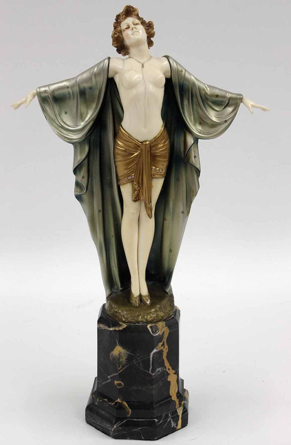 'Spring Awakening'<br> (also known as 'INVOCATION')<br>By Ferdinand Preiss (1882-1943) Circa 1920<br>A bronze and ivory female bare-breasted<br>dancer wearing a gold coloured tunic, with<br>a cloak draped over her arms, hanging in<br>deep folds to the ground.  She is wearing<br>a pair of low-healed shoes, and stands on<br>a rough bronze circular base, which tops an<br>eight-sided portoro marble base. Her hands,<br>torso, head and legs are in ivory.<br>The cloak is patinated in a pale<br>blue over a silver ground.<br>Height: 35.6 cms<br>Signatures:  Engraved 'F Preiss' <br>on the bronze base.<br>Reference: (i) Bryan Catley, Art Deco<br>and Other Figures, Antique Collectors' Club,<br>London, 1978, pictured p. 252.<br>(ii) Alberto Shayo, Ferdinand Preiss,<br>Art Deco Sculptor, The fire <br>and the flame, Antique Collectors' Club, 2005<br>pictured p. 179. <br>(iii) Victor Arwas, Art Deco<br>Sculpture, London, 1992,<br>pictured p. 184 and 185.