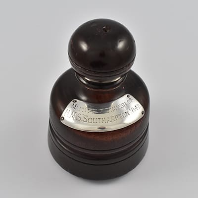 A turned teak paperweight made from the timber of the ship that saved Natal. Applied with a silver plaque inscribed 'MADE FROM TIMBER OF H.M.S. SOUTHHAMPTON 1842'.