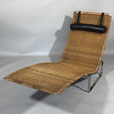 Poul Kjaerholm (Danish 1929-80). PK24 chaise longue, c.1970. E. Kold Christensen, Denmark. Designed in 1965 with a polished stainless steel frame, cane seat & leather cushion. 87 x 155 x 67 cm.